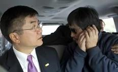 An handout photo from US Embassy Beijing Press office shows blind activist Chen Guangcheng (R) making a phone call as he is accompanied by U.S. Ambassador to China Gary Locke in a car on the way to a hospital in Beijing, May 2, 2012.