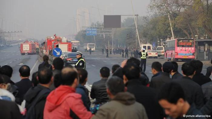 epa03937656 Onlookers watch policemen working at the site of explosions outside the provincial headquarters of China